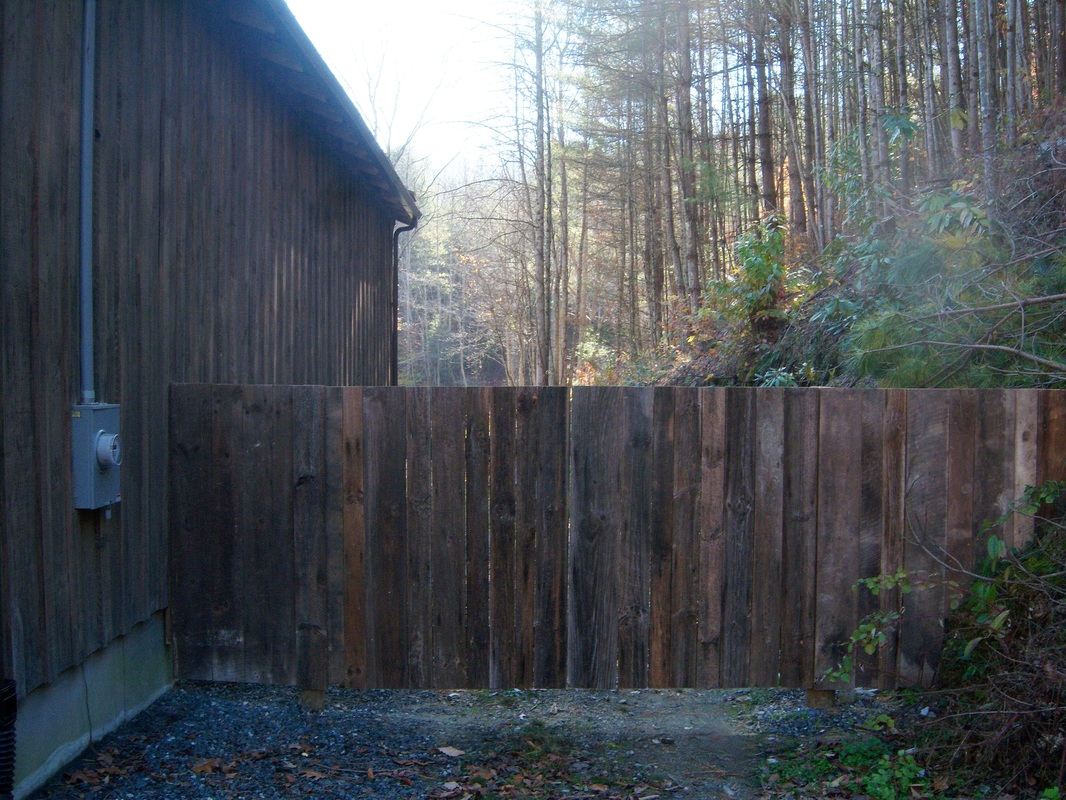 Picture of a driveway gate next to a barn