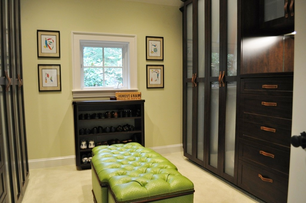 A master closet with a tufted leather ottoman in the middle